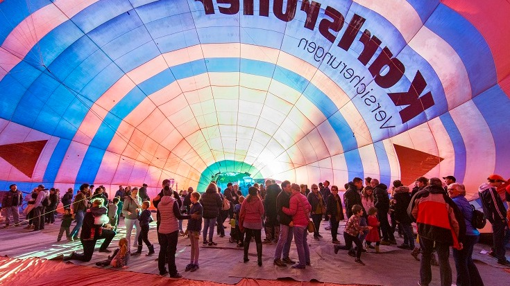 A crowd of people inside a rainbow coloured hot air balloon on its side with the opening in the centre back of photo