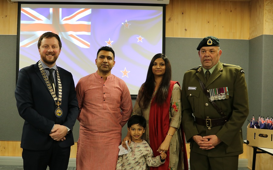 Mayor Sam Broughton and Major Grant Payton stand either side of an Indian man, woman and child in traditional dress