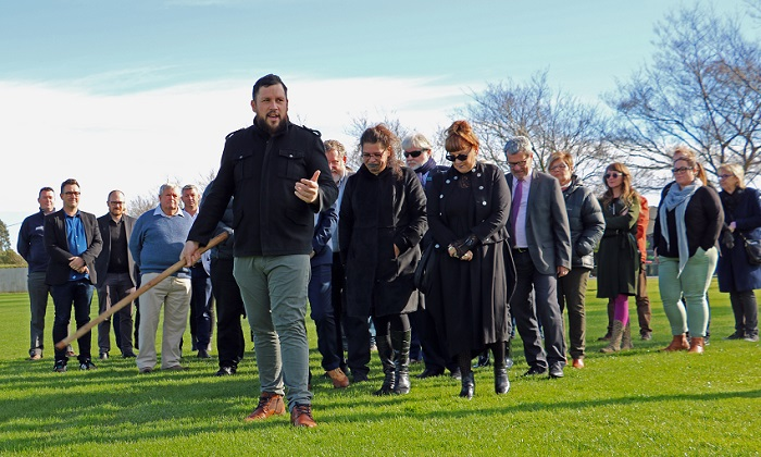 A young maori man with a beard and a black jacket gestures with a tokotoko as he leads a group walking with bowed heads across a park