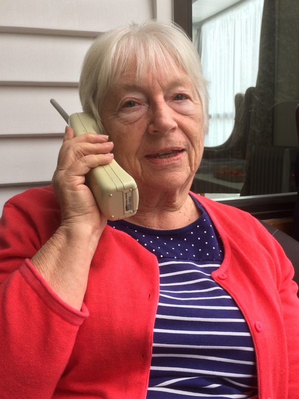 Older lady, short white hair and red jacket talking on a cordless phone