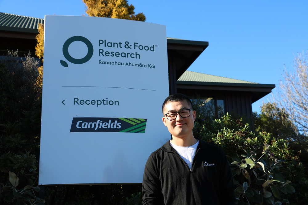 A smiling man standing in front of a sign for Plant and Food Research