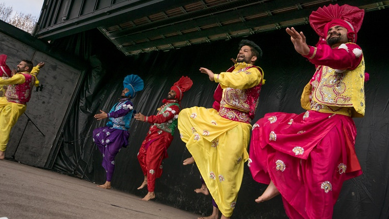 Five men in brightly coloured traditional Indian outfits in red, yellow, pink, purple and blue dance on a stage