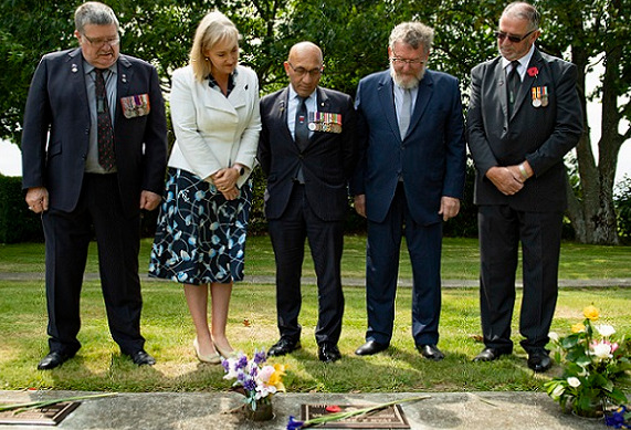 Dignitaries RNZRSA president BJ Clark, Selwyn MP Amy Adams, Minister for Veterans Ron Mark, Selwyn Deputy Mayor Malcolm Lyall and RSA Canterbury District President Stan Hansen stand in a line with heads bowed looking at one of the newly unveiled plaques