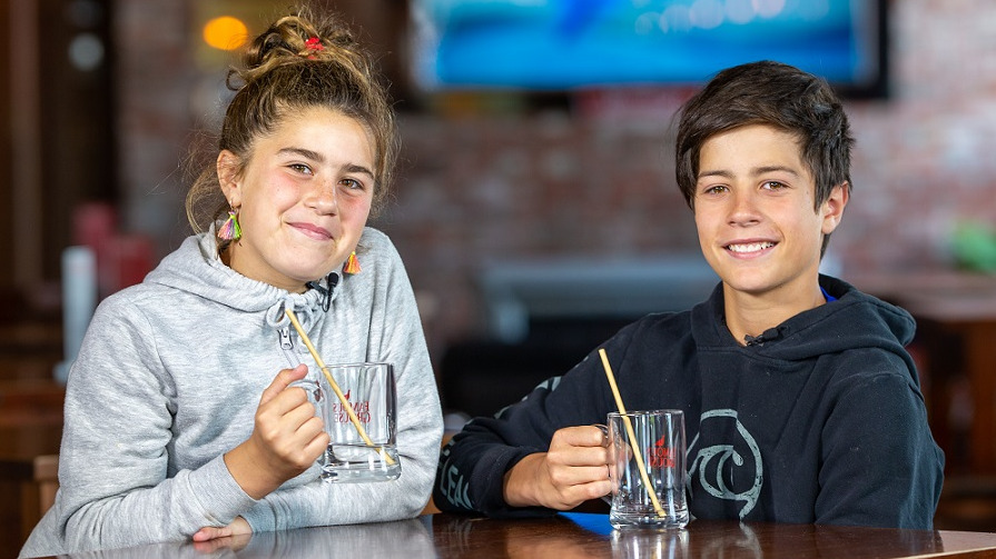 Girl with brown hair and grey hoodie and boy with black hair and black hoodie sit at a wooden table in a bar holding beer glasses with metal straws in them
