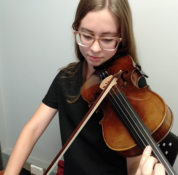 Close up of teenage girl with brown hair and glasses playing the violin
