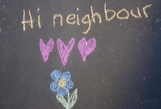 The words hi neighbour written in chalk on a pavement with a drawing three love hearts and a flower