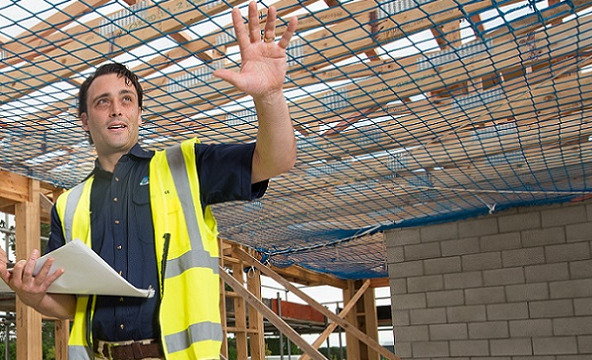 A building inspector gesticulates as they look through a building site