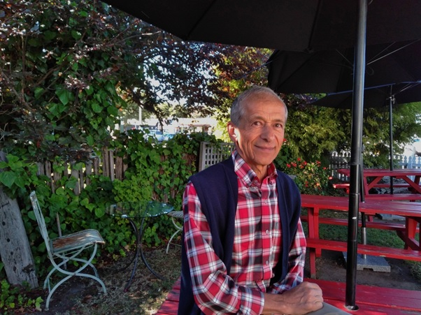 Man with receeding grey hari, red check shirt and blue gilet sits at an outdoor cafe table