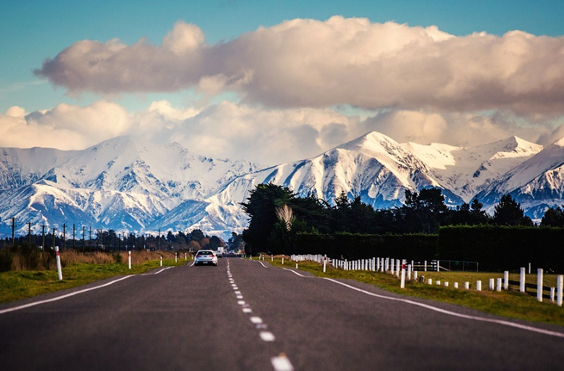 A road stretching towards snowy mountains