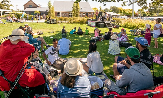 A crowd watches a band perform on the Lincoln Green for Summer in Selwyn