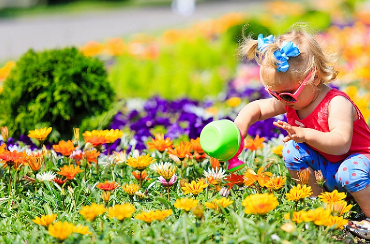A toddler in sunglasses watering a brightly coloured flower bed