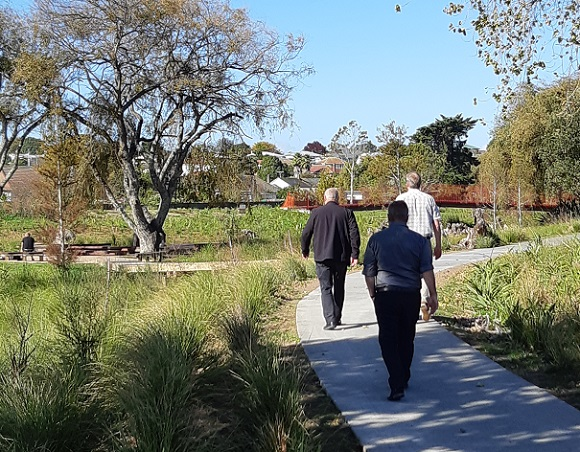 Three men walking away from the camera down a path through a park