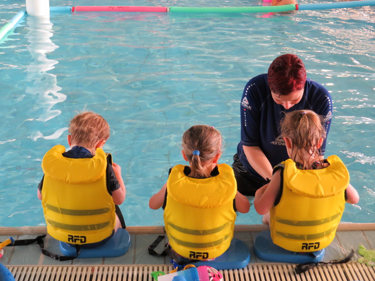 Instructor teaching pre school kids to swim