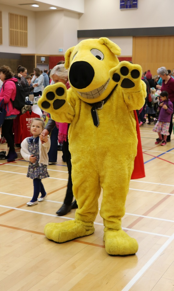 Yellow mascot dog CoolStuff waves at camera in front of children playing in a gym