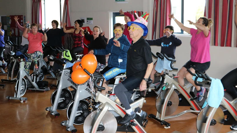 A man in a black top, wearing a pink hat with candles on it rides an Exercycle with orange balloons on the front while a group of people around him Excercycles wave their hands in the air