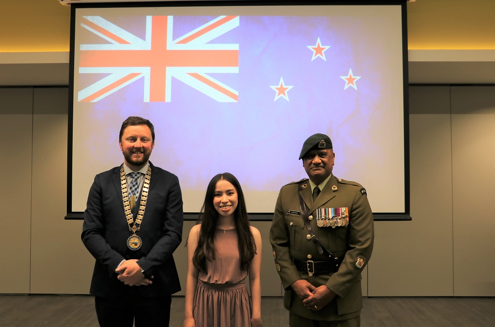 Mayor Sam Brougton in a blue suit and wearing his mayoral chains stands with a shorter woman in a grey dress and a Maori man in NZ Army dress uniform with a New Zealand flag on a scree behind them