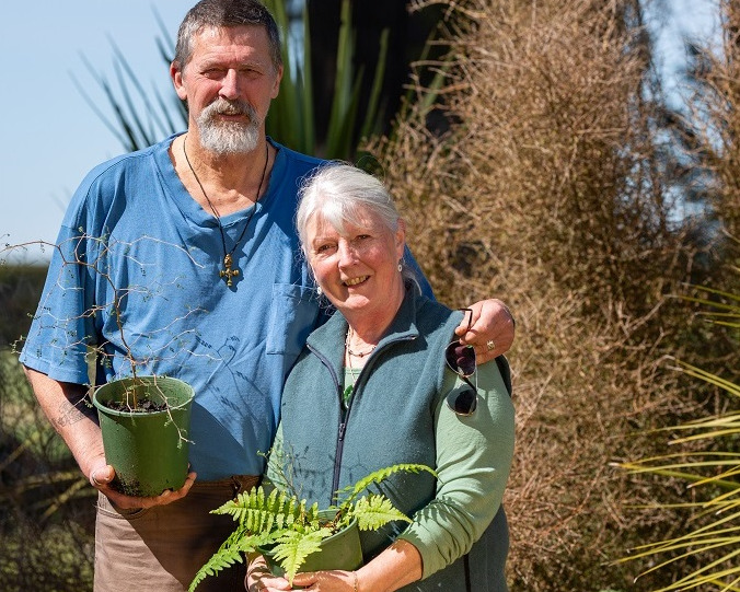 Stephen Clarke, in a blue shirt t-shirt stands with his arm around Lesley Barlow in a green gilet and shirt, while they both hold plants in pots