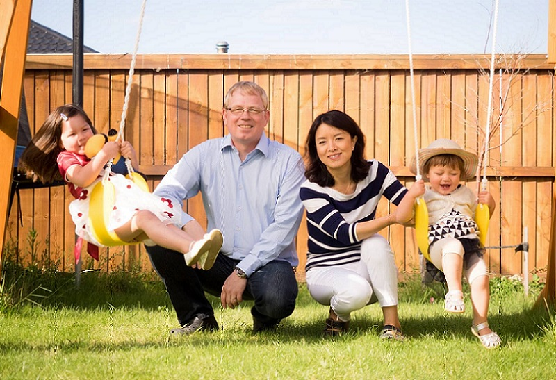 Two smiling parents crouch in between two children on swings in a garden