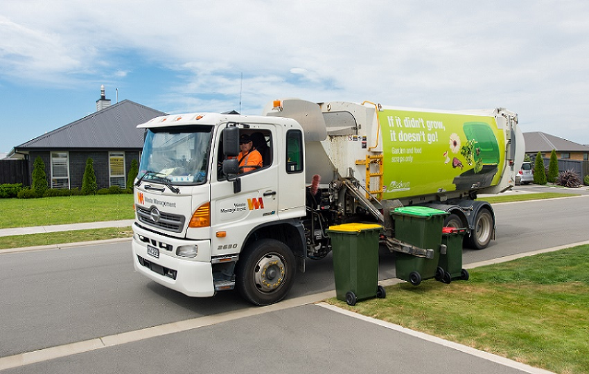 A rubbish truck on a suburban street lifting a green organics bin