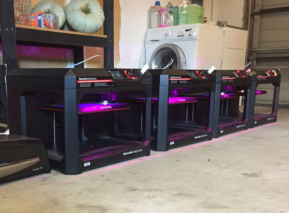 A row of 3D printers in a garage