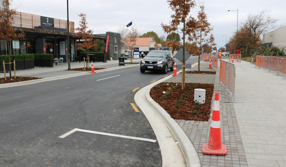 A black car drives down the newly reopened section of Tennyson Street, between the wider pedestrian walkways