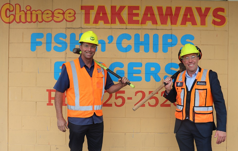 Council Grant Millar and Group Manager Property Douglas Marshall stand in front of the Chinese takeaway building in hard hats, hi-vis vests and goggles, holding sledgehammers