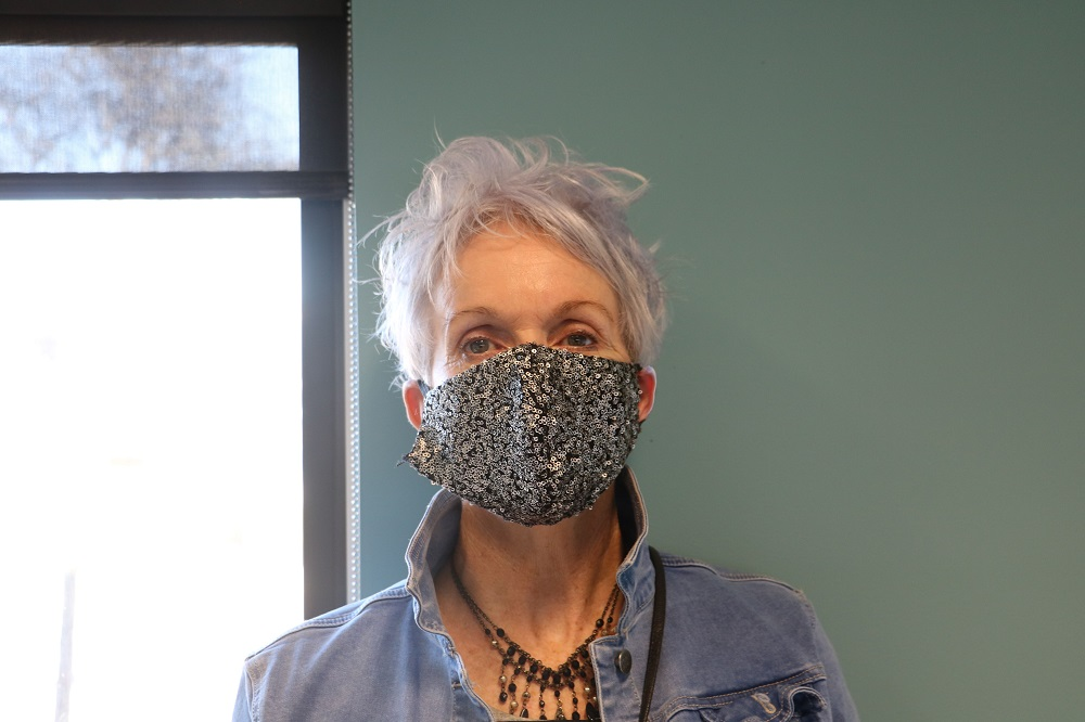 Image of a woman in a black mask with silver sequins