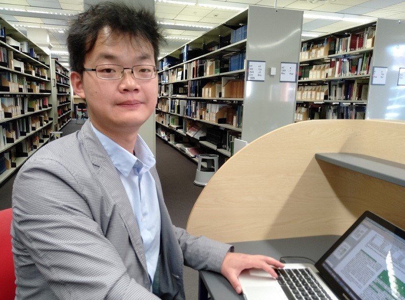 A Chinese man in a suit jacket and business shirt sits using a computer in a library