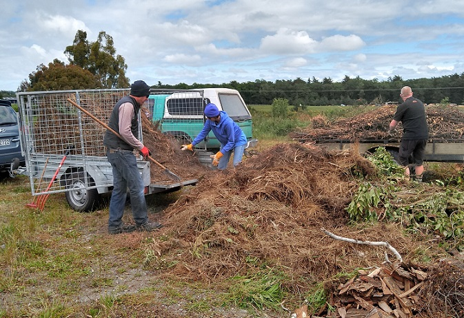 Three people unloading trailers of green waste into a pile