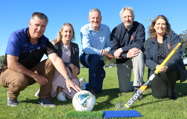 Five people, one holding a football, one holding a hockey club, crouch on a grass field behind two pieces of artificial turf