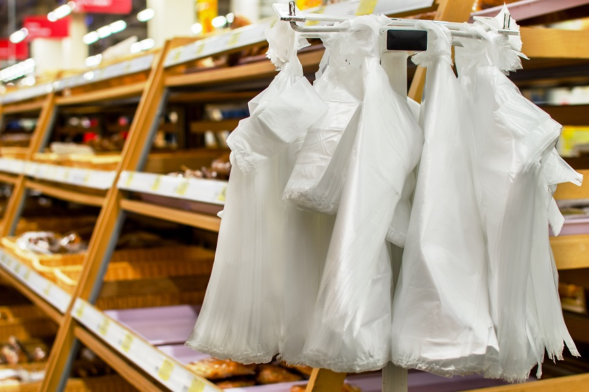 A two piles of white plastic bags hang vertically off a metal hook in front of some wooden shelves