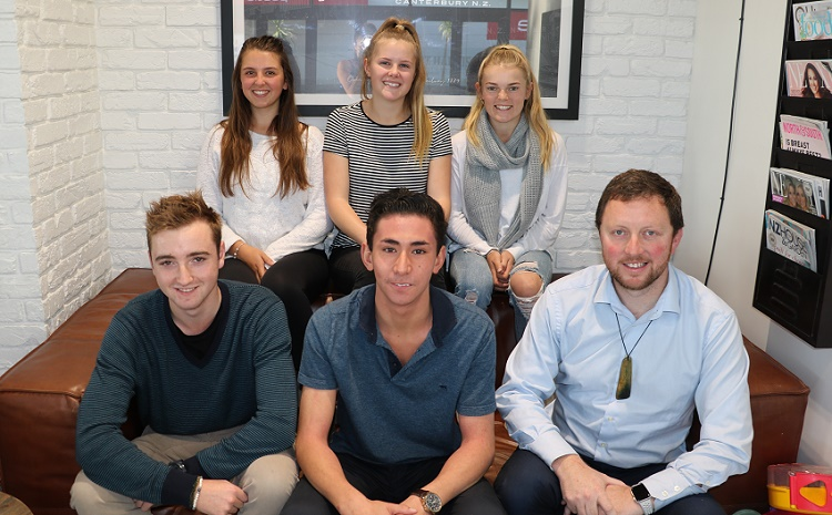 Mayor Sam Broughton with past scholarship winners sitting on a brown couch in front of a white painted brick wall. Two teenage boys sitting on front of the couch, three teenage girls sitting behind