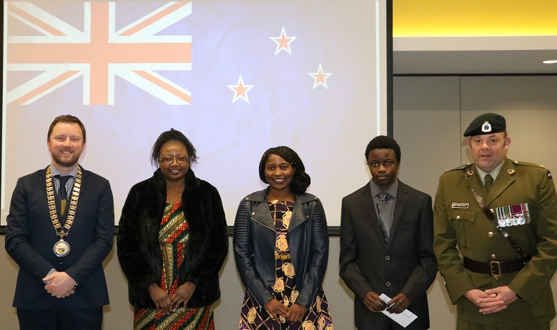 Five people, Mayor Sam Broughton,  Dorothy Chilwalo, Angela Yendama, Chinjila Lunda and Major Grant Payton in army uniform stand in a line in front of a screen with the New Zealand flag projected on it