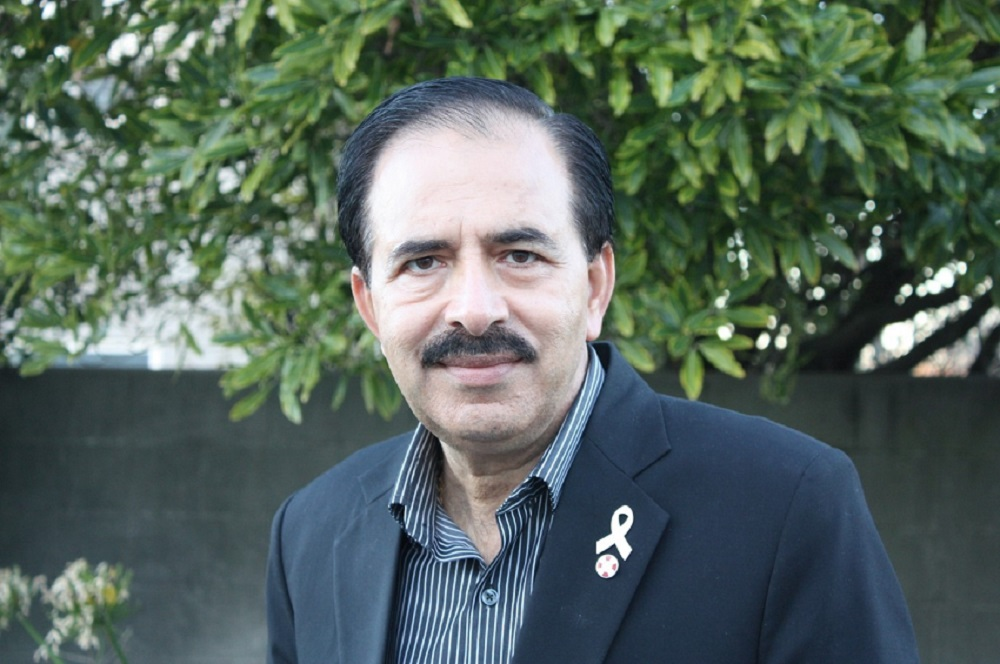 A middle-aged Middle Eastern man with receding black hair, black mustache and wearing a black suit jacket with a white ribbon lapel pin stands in front of a breeze block wall with a tree growing over the top