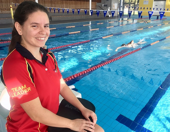 Woman with black hair wearing red and black shirt with team leader on sleeve sits on side of pool