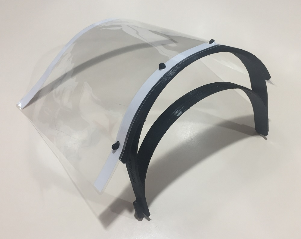 A clear face mask with black clips on a white background