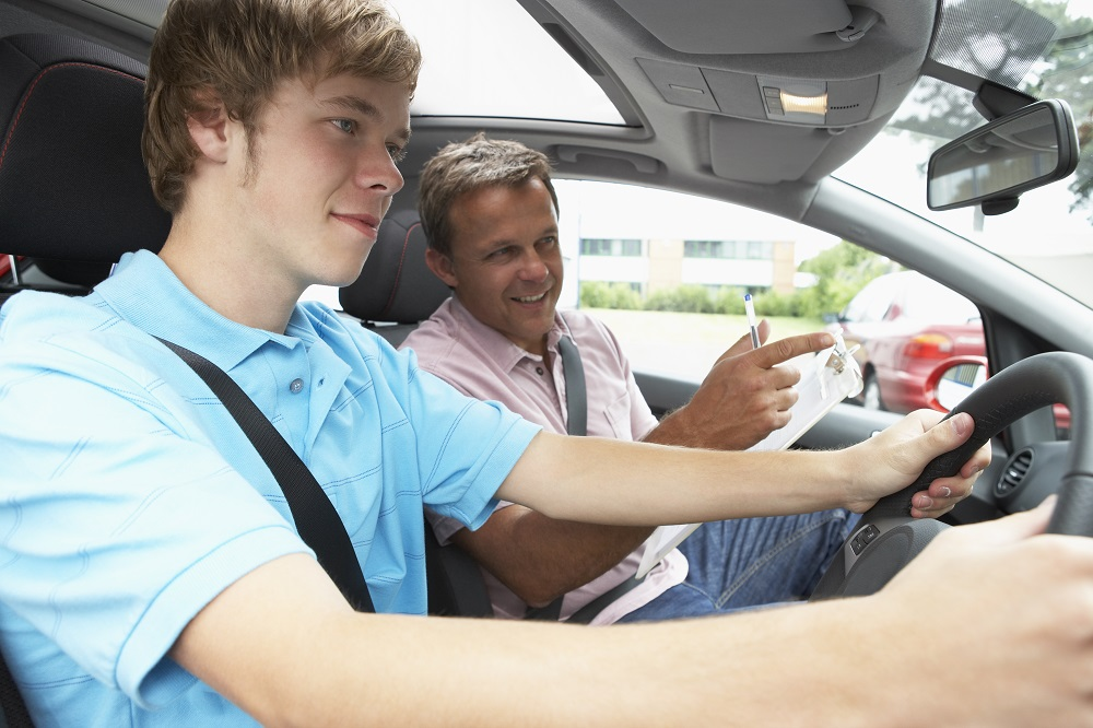 Teenager in a blue polo shirt drives a car while a man with a clipboard and a pen points and gives an instruction