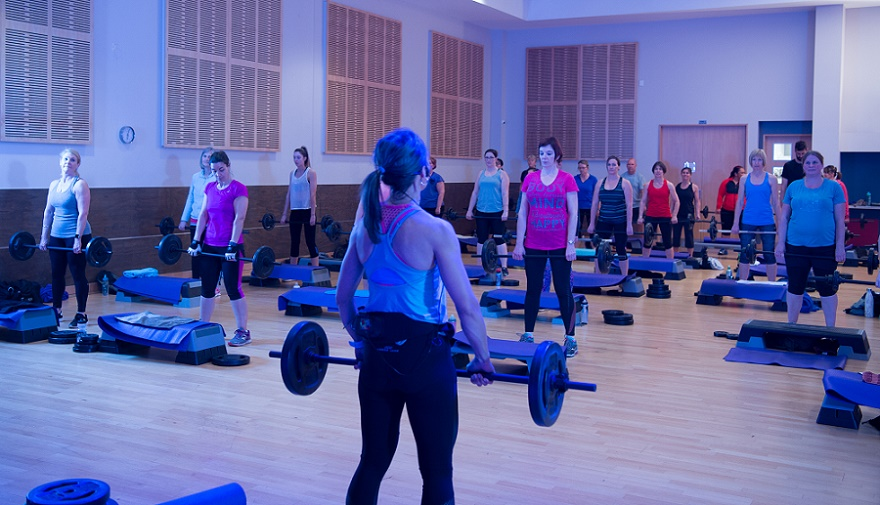 A women's pump class with a group holding weights under purple lights