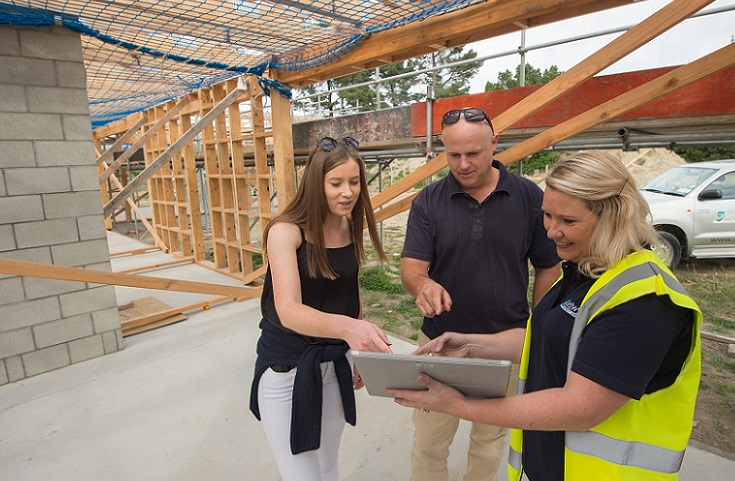 A Council staff member in a high-viz jacket shows a man and woman something on a tablet as they look round a building site