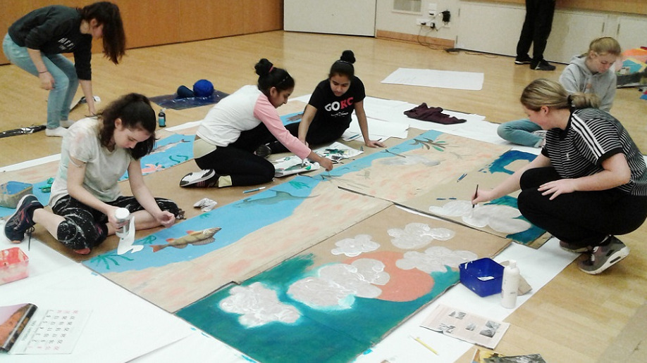 A group of students sitting on the floor painting a nature scene on large wooden boards