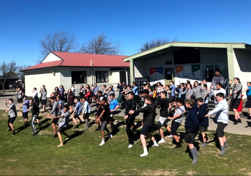 A group of students performing kapa haka in front of a school classroom