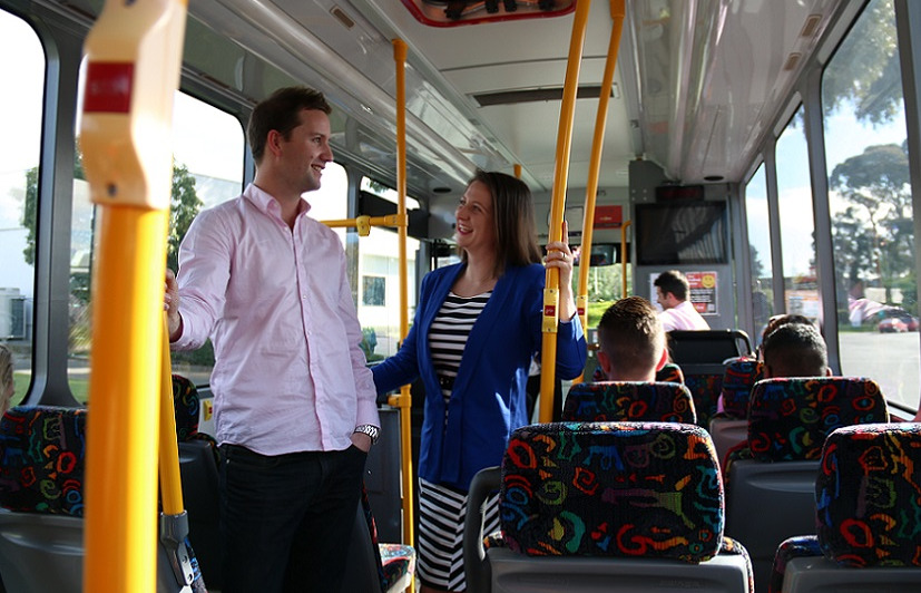 A man and a woman talk while standing on the bus