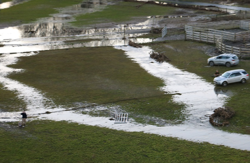 A flooded field and muddy, boggy ground round its fence