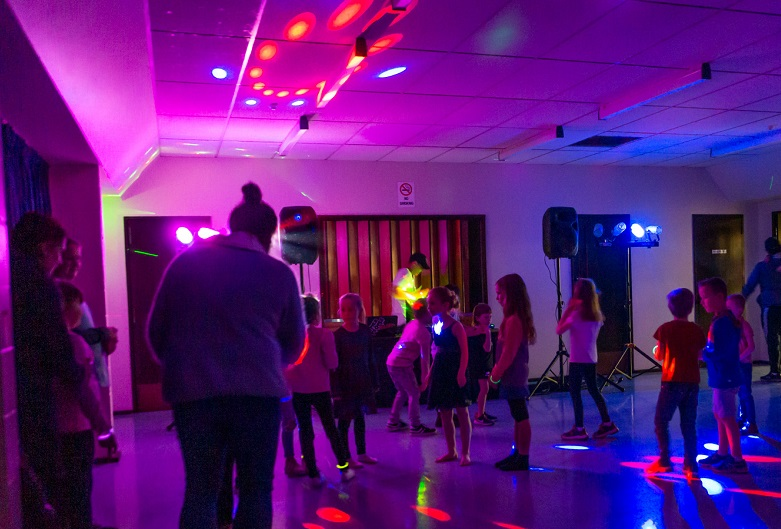 Children dancing at DiscoMania in a hall lit in multi coloured disco lights
