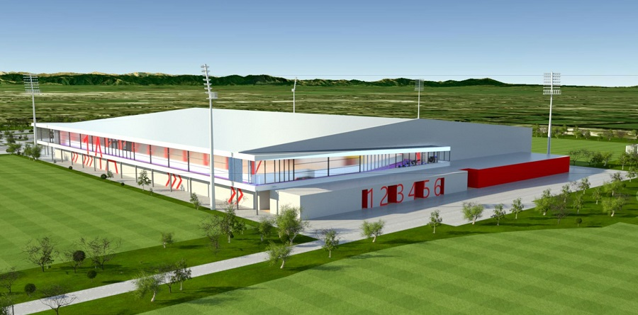 An artists impression of the new indoor courts showing an aerial view of a red and white building on the edge of two grass fields