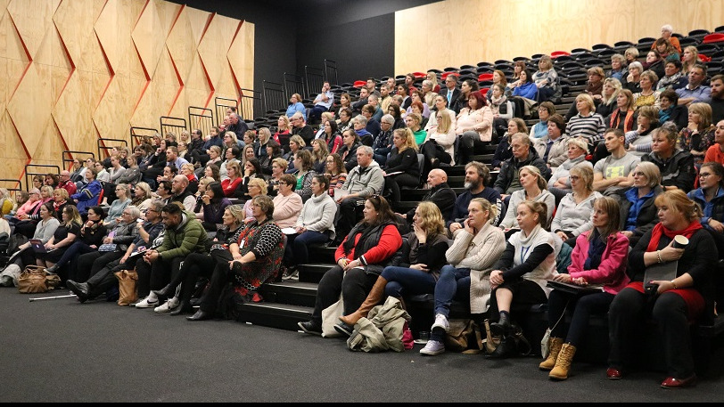 A crowd of over 100 people sitting in the Rolleston College auditorium