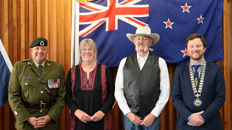 A man in Army dress uniform, a blonde woman in a black top, a man in a large white stetson hat with a bushy grey moustache and Mayor Sam Broughton in his mayoral chains stand in front of a New Zealand flag
