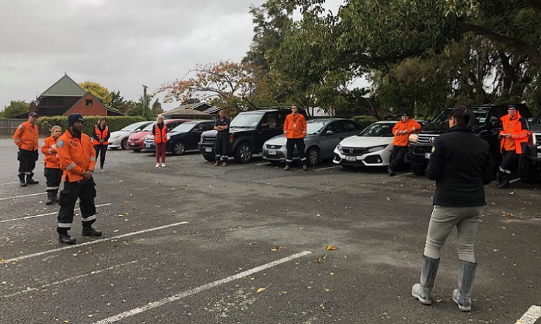 A group of men and women in orange jackets spaced through a car park some standing next to cars, listening to a woman with back to camera giving instructions