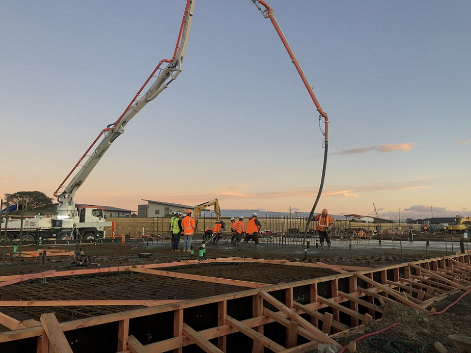 View across work site in early morning, truck with high arching hose pours concrete, spread by workers in hi-vis