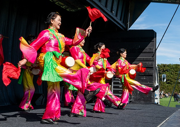 A group of women in brightly coloured traditional Chinese dress dance on the stage at CultureFest